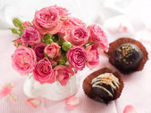 Pink roses with candys — Stock Photo