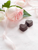 Pink rose with chocolate candies — Stock Photo