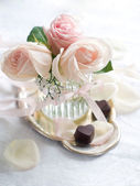 Cream roses and candies — Stock Photo