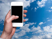 Smartphone held in the hand on a sky background — Stock Photo