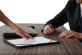 Female hand pointing to businessman at signature place on a contract document — Stock Photo