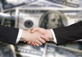 Business handshake on the background of money — Stockfoto