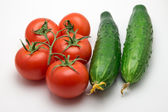 Five tomatoes and two cucumber — Stock Photo