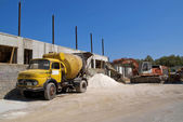 Cement mixer truck and digger — Stock Photo