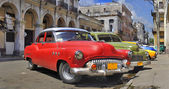 Havana street with colorful old cars in a raw — Stock Photo
