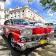 Red car under tree branches in havana, cuba — Stock Photo #48572313