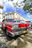 Red car under tree branches in havana, cuba — Stock Photo