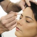 Hands applying make up on hispanic girl — Stock Photo #49168585