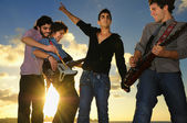 Young musical band with instruments at sunset — Stock Photo