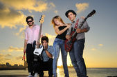 Cool young musical band posing at sunset — Stock Photo