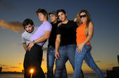 Treandy team of young people posing at sunset — Stock Photo