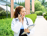 Smiling female doctor on phone — Stock Photo