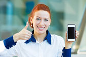 Happy woman showing her smart phone giving thumbs up — Stock Photo