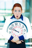 Anxious businesswoman holding clock — Photo