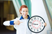Business woman pointing on wall clock — Stock Photo