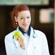 Doctor offering green apple — Stock Photo #48278353