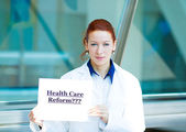 Confused doctor holding health care reform???sign — Stock Photo