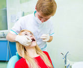 Dentist examining young adult patient — Stock Photo