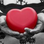 Hands senior, elderly woman holding red heart — Stock Photo