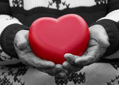 Hands senior, elderly woman holding red heart — Stock Photo