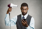 Businessman texting while using haidryer — Foto de Stock