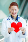 Female doctor holding red heart — Stock Photo