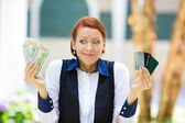 Confused woman holding credit cards and cash — Stock Photo