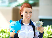 Businesswoman holding piggy bank, dollar bills — Stock Photo