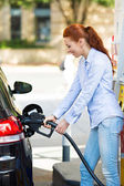 Woman at gas station, filling up her car — Stock Photo