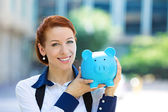 Happy woman, corporate employee holding piggy bank — Stock Photo