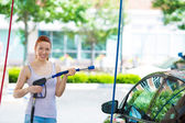 Smiling young woman washing, cleaning her compact car — Stock Photo