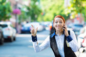 Young business woman talking on smart phone, hails taxi cab — Stockfoto