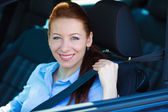 Woman pulling on seatbelt inside black car. Driving safety — Stock Photo