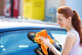 Woman cleaning , dry wiping her black car on summer sunny day — Stock Photo