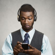 Corporate executive with headphones holding mobile phone — Stock Photo