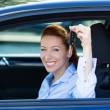 Happy, excited woman showing keys from her new car — Stock Photo