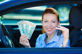 Woman holding car keys, dollar bills, sitting in her new car — Stockfoto