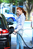 Attractive woman refueling her car at gas station — Stock Photo
