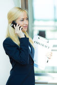 Businesswoman talking on a phone, holding contract documents — Stock Photo