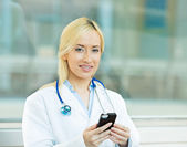 Female health care professional, doctor holding smart phone — Zdjęcie stockowe