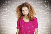 Stressed young student standing in front of a blackboard filled  — Stock Photo