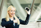 Happy woman pointing at her smart phone — Stock Photo