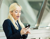 Surprised business woman reading something from her smart phone — Stock Photo