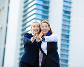 Two excited business women, friends giving victory sign, gesture — Stock Photo