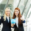 Portrait two happy business women holding piggy bank giving thum — Stock Photo #50025639