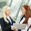 Happy businesswomen smiling, discussing a deal, holding computer — Stock Photo #50025623