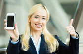 Happy excited businesswoman showing her smart phone — Stock Photo