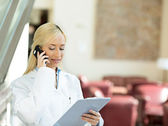 Happy female doctor talking to a patient on a phone — Stock Photo