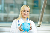 Happy health care professional, doctor, nurse holding piggy bank — Stock Photo