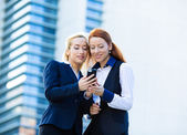 Happy business women reading something on mobile, smart phone — Stock Photo